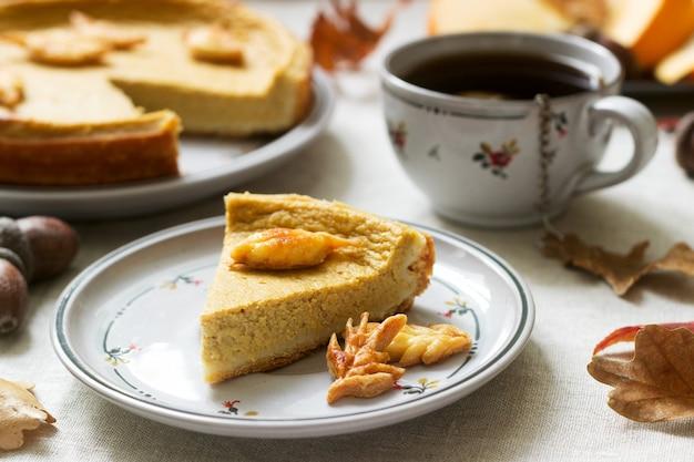 カボチャと紅葉の背景にクッキーで飾られた伝統的なアメリカのカボチャの自家製ケーキ。