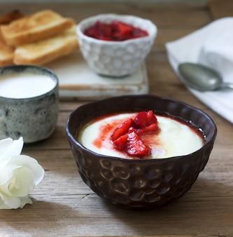 Домашний завтрак из манной каши, клубничным соусом, кофе с молоком и тост на деревянной поверхности.