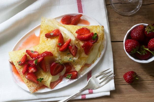 Тонкие блинчики с кремовой начинкой и клубничным соусом на деревянном столе. деревенский стиль