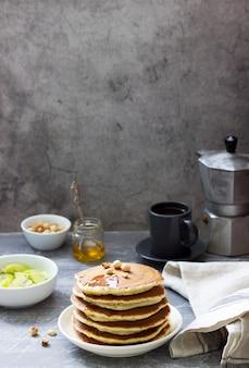 Вегетарианский завтрак из блинов, кофе, меда, орехов и фруктов.