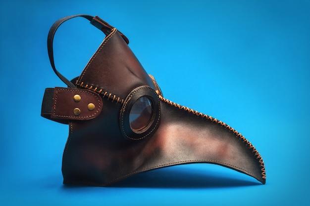青色の背景に分離されたペストドクターマスク。医療用顔面シールド。