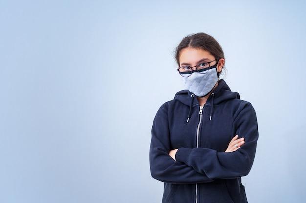 Девушка подростка в медицинской маске стоит пересеченные оружия, на холодной серой предпосылке с космосом экземпляра. вирус.