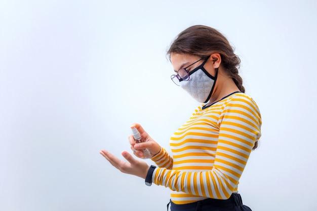 Девушка в медицинской маске лечит руки антисептиком, на холодном сером фоне с копией пространства. вирус