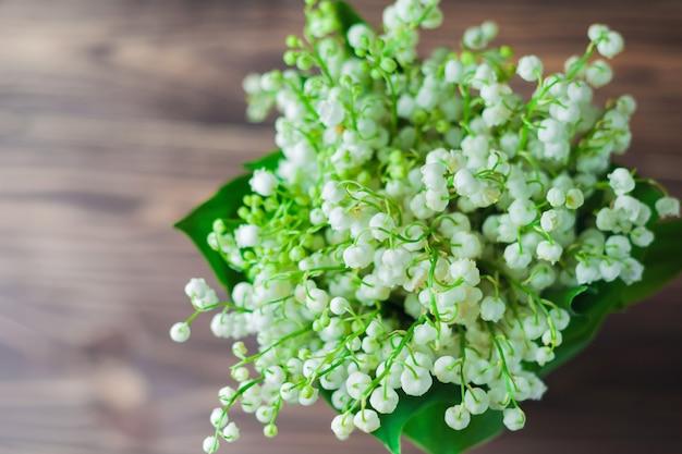 スズランの花、木製の背景に。