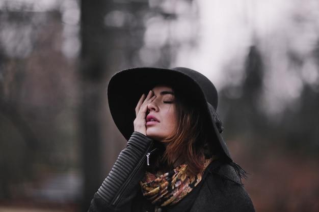 秋の公園を歩いて白い綿のドレスと暗いコートを着た魅力的で魅力的な若い女性。