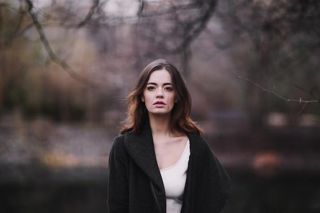 秋の公園を歩いて白いドレスとコートの魅力的な魅力的な若い女性。