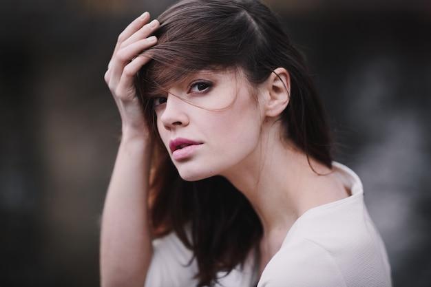 秋の公園で黒髪と美しい首を持つ魅力的な若い女性。