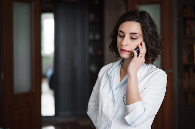 Молодая брюнетка женщина-врач в белом халате, разговаривает по телефону в комнате.