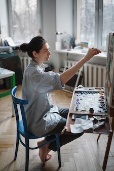 若い女性アーティストが青い椅子のある明るいスタジオに座って、イーゼルに油絵を描きます。