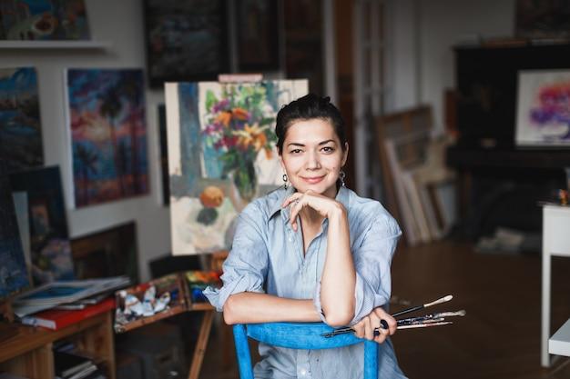 スタジオで若い笑顔ブルネットの女性アーティスト