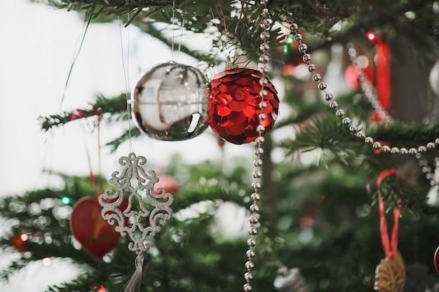 Рождество разнообразные украшения и шишки на искусственной елке.