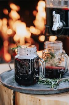 グリューワインと燃える暖炉のあるクリスマステーブルの装飾