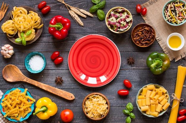 木製の背景、トップビューで野菜、健康またはベジタリアンの概念のさまざまな種類のパスタの種類