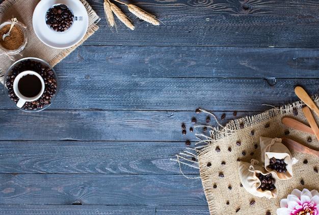 コーヒー豆と異なる木製の背景に他のコンポーネントとコーヒーのカップ。