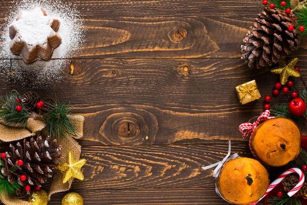Мини-панеттоне с фруктами и рождественские украшения, деревянный фон