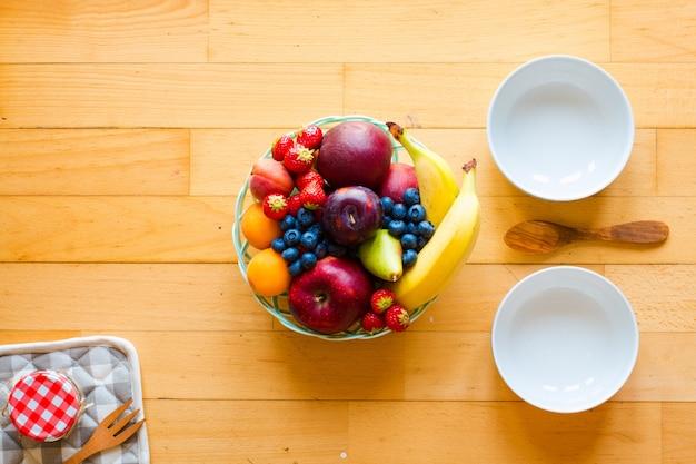 Чаша из свежих фруктов с бананом, яблоками, клубникой, абрикосами, черникой, сливами, цельными зернами, вилками, вид сверху