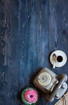Старый старинный телефон, с бискотти, кофе, пончики