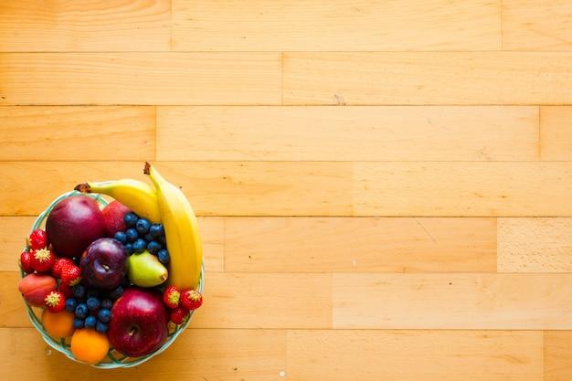 Чаша из свежих фруктов с бананом, яблоками, клубникой, абрикосами, черникой, сливой, цельнозерновыми вилками, вид сверху