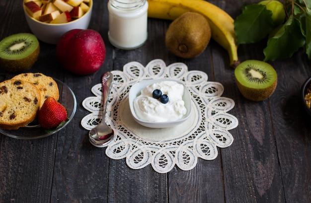 素朴な木製のヨーグルトイチゴブルーベリーアップルバナナと健康的な朝食用シリアル。上面図