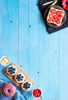 Вкусные здоровые фрукты завтрак бутерброды с различными начинками сыр банан клубника рыбалка масло черники на другой деревянный фон.