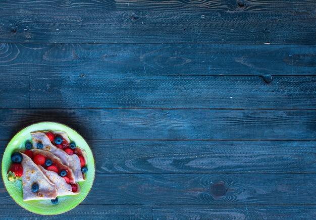 新鮮な自家製クレープは、イチゴと暗い背景の木にブルーベリーのプレートで提供しています