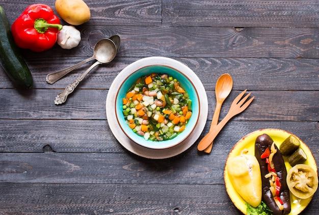 Суп из свежих овощей, приготовленный в домашних условиях на деревенском деревянном столе
