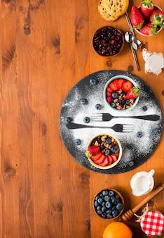 Зерновой. завтрак с мюсли и свежими фруктами в мисках на деревенском деревянном фоне