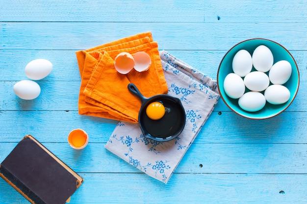 Куриное яйцо с кухонной утварью на деревянном столе