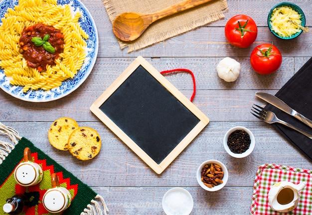 フジッリパスタトマトソーストマトオニオンニンニク乾燥パプリカオリーブピーマンと木製の背景にオリーブオイル。