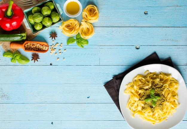 Паста тальятелле с соусом песто и другими овощами на фоне дерева. вид сверху
