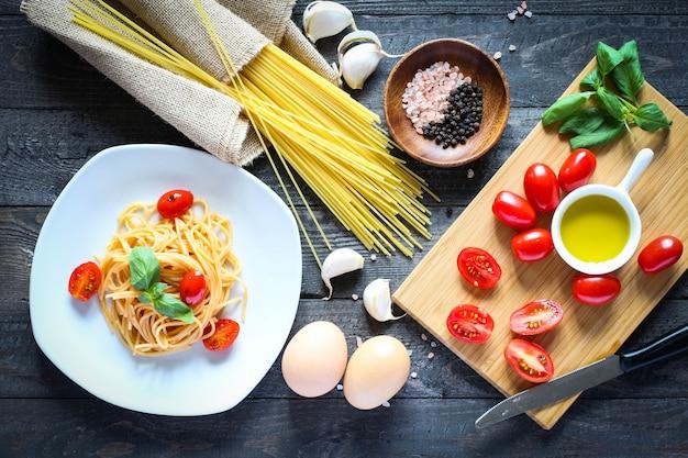 Взгляд сверху итальянских ингридиентов для томата и базиликовых спагетти.