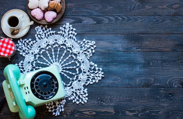 Старый старинный телефон с бискотти кофе пончики на деревянном фоне