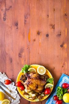 Домашняя запеченная курица с лимоном и картофелем на деревянной поверхности