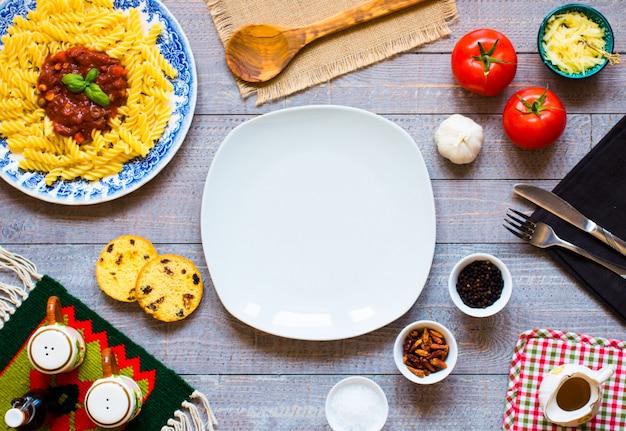 木製のテーブルにトマトソースとより多くの食材を使ったフジッリパスタ