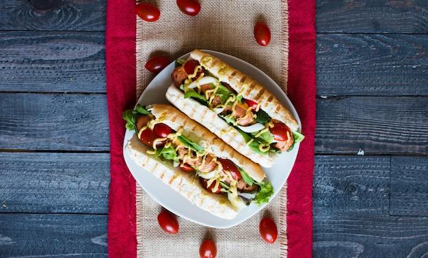 ピクルス、トマト、オリーブのホットドッグ