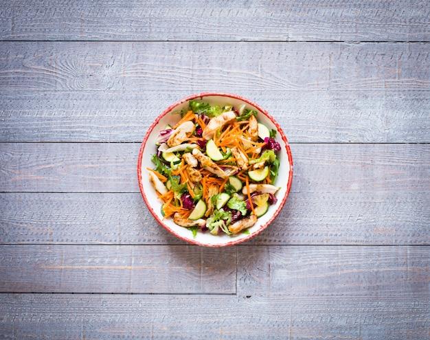 木製の表面にズッキーニとチェリートマトと鶏の胸肉のサラダ