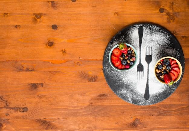 Зерновой. завтрак с мюсли и свежими фруктами в мисках на деревенской деревянной поверхности,
