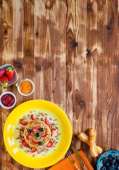 新鮮なベリー、イチゴ、ブルーベリー、メープルシロップと木製の表面の自家製パンケーキ。