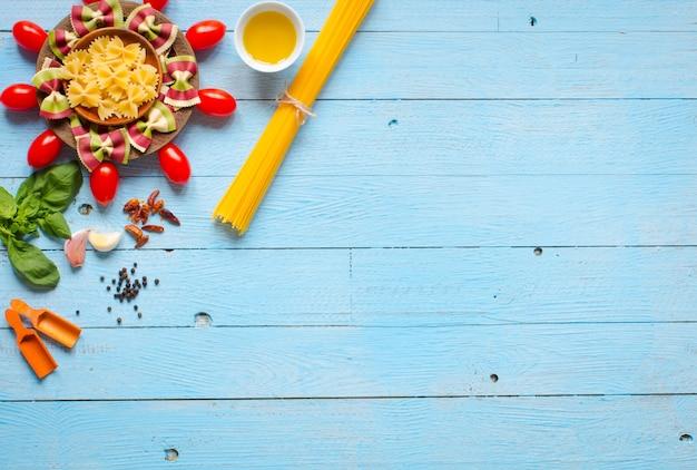 パスタの背景。野菜とハーブ入りの数種類の乾燥パスタ。上面図