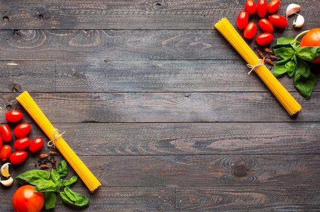 Паста фон. несколько видов сухой пасты с овощами и зеленью. вид сверху