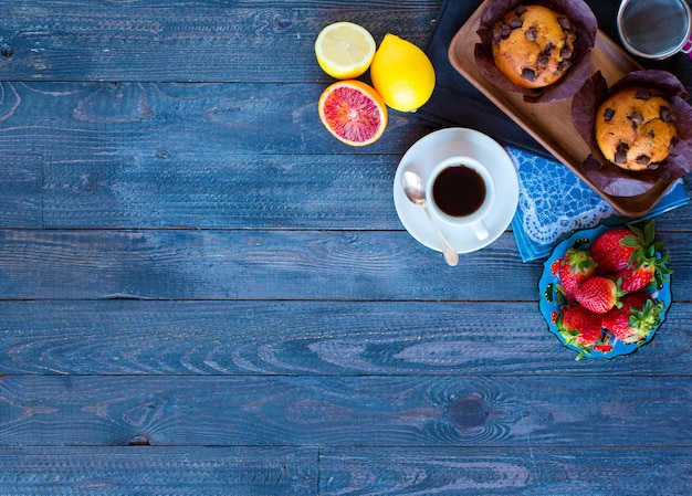 木製のテーブルにさまざまなペストリーや果物とコーヒーと紅茶を朝食します。