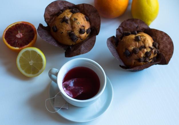 Завтрак с кофе и чаем с различными пирожными и фруктами на белом деревянном столе