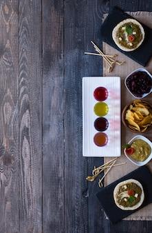 木製の背景にアボカド、トマト、チーズ、ハーブ、チップス、お酒とおいしいとおいしいブルスケッタ。