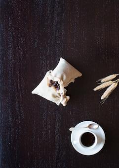 コーヒー豆と異なる木製のテーブルの他のコンポーネントとコーヒーのカップ
