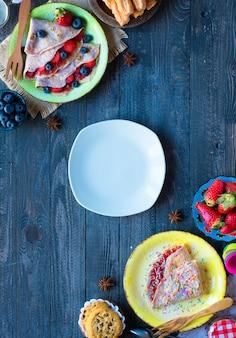 Свежие домашние блины подаются на тарелке с клубникой и черникой, на темном деревянном столе