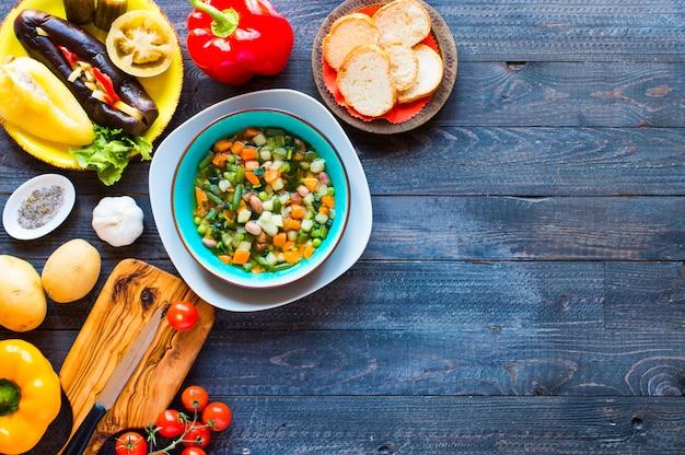 木製の素朴なテーブル、トップビューで、家庭で作られた新鮮な野菜スープ