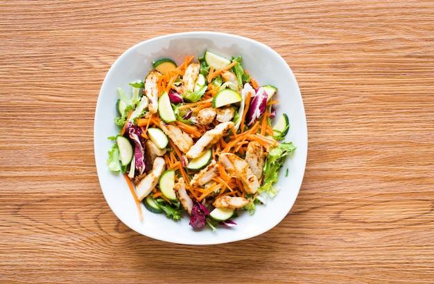 木製テーブルの上のズッキーニとチェリートマトの鶏の胸肉のサラダ