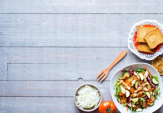 Салат из куриной грудки с цуккини и помидорами черри, на деревянном фоне