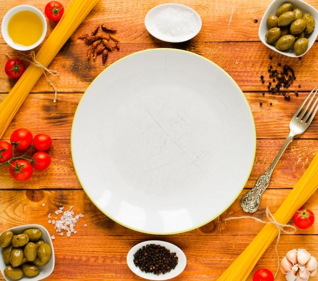 Паста с томатным соусом и другими компонентами на деревянном фоне