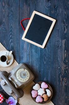 Старый старинный телефон, с бискотти, кофе, пончики на деревянном фоне